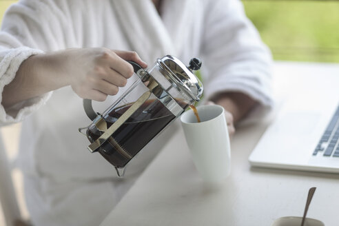 Close-up of man with coffee plunger using laptop - ZEF005359