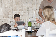 Family having lunch at dining room table with boy holding digital tablet - ZEF005376