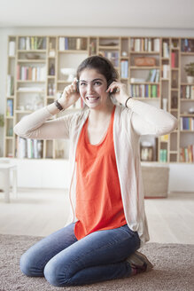 Young woman hearing music with headphones at home - RBF002874