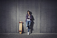 Young woman standing besides her longboard - RBF002882