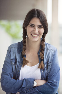 Portrait of smiling young woman with braids - RBF002885