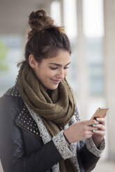 Portrait of smiling young woman with smartphone - RBF002887