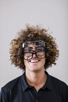 Portrait of smiling man with curly hair wearing four different glasses - EBSF000840