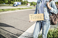 Germany, female hitchhiker with sign 'future' waiting at roadside - RIBF000081