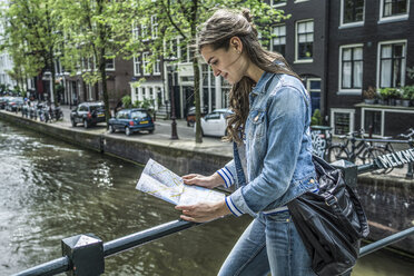 Netherlands, Amsterdam, female tourist looking at city map in front of town canal - RIBF000085