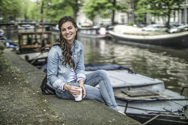 Netherlands, Amsterdam, portrait of female tourist having a rest - RIBF000086