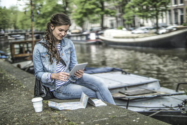 Netherlands, Amsterdam, female tourist using digital tablet in front of town canal - RIBF000088
