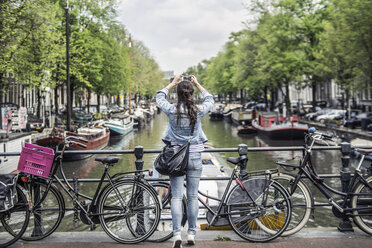 Netherlands, Amsterdam, female tourist taking a selfie with smartphone - RIBF000089