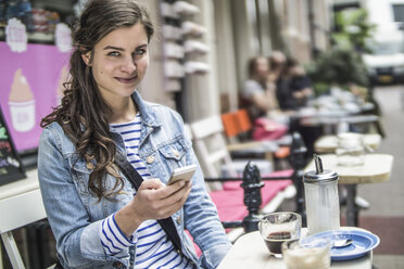 Netherlands, Amsterdam, portrait of female tourist sitting in a street cafe - RIBF000092