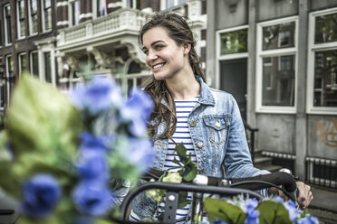 Netherlands, Amsterdam, smiling woman with bicycle - RIBF000096