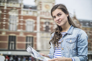 Netherlands, Amsterdam, woman with city map in front of central station - RIBF000108