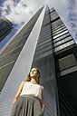 Spain, Madrid, young woman in front of a skyscraper - ABZF000077