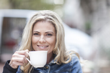 Portrait of smiling woman drinking coffee - ZEF006569