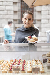 Young woman selling pastries at market - ZEF006571