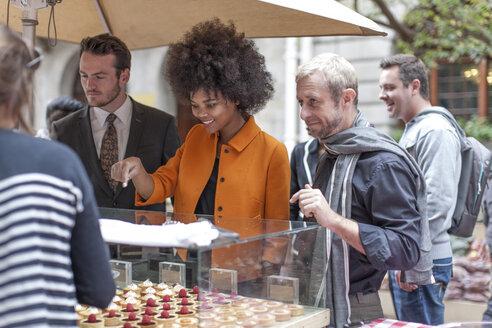 Woman choosing pastries at food stall at city market - ZEF006582