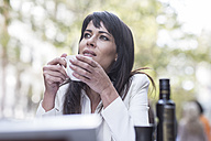 Woman drinking coffee at outdoor cafe - ZEF006591