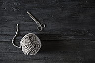 Scissors and grey ball of wool on black wood - PDF000963