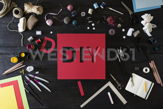 Craft materials, tools and red cardboard with the word DIY on black wood - PDF000957