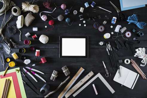 Arrangement of craft materials, tools  and digital tablet on black wood - PDF000954