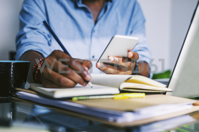 Man at home office holding smartphone making a note - EBSF000642