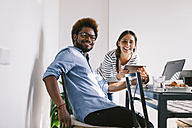 Smiling young man and woman working with laptop and digital tablet at home office - EBSF000659