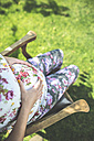 Pregnant woman sitting on wooden chair in a garden - DEGF000421