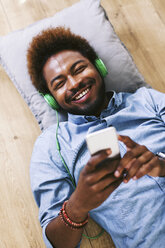Young Afro American man lying on floor with headphones and smart phone - EBSF000613
