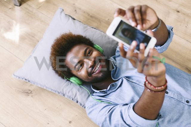 Young Afro American man lying on floor, taking selfie - EBSF000614