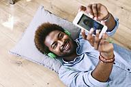 Young Afro American man lying on floor, taking selfie - EBSF000614