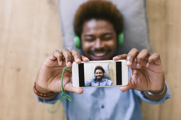 Young Afro American man lying on floor, taking selfie - EBSF000616