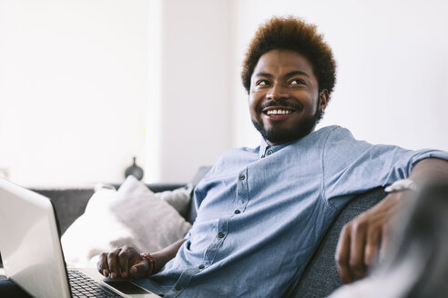 Young Afro American man sitting on couch, using laptop - EBSF000621