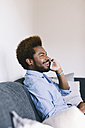 Young Afro American man on the phone, sitting on couch - EBSF000623