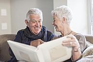 Senior couple watching photo album together - ZEF005509