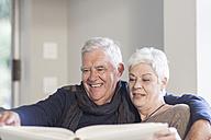 Senior couple watching photo album together - ZEF005512