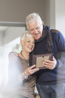 Senior couple looking together at picture frame - ZEF005515