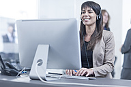 Woman with headset working in office - ZEF005589