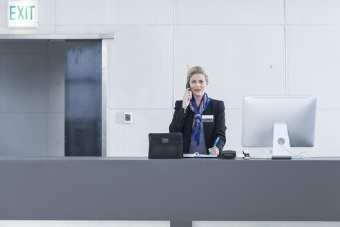 Woman behind reception desk in hotel lobby on the phone - ZEF005613