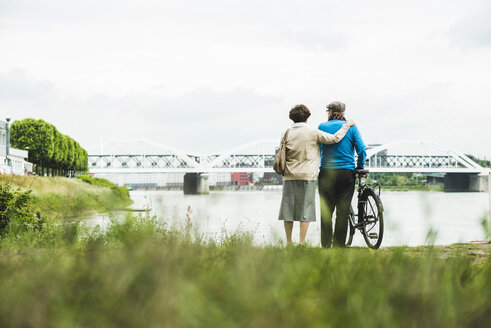 Back view of senior couple standing at water's edge with bicycle - UUF004495