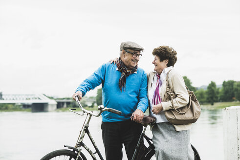 Happy senior couple standing at water's edge with bicycle - UUF004498