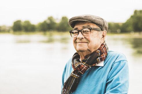 Portrait of smiling senior man wearing glasses and cap - UUF004503
