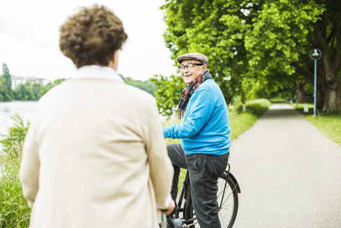 Happy senior man with bicycle face to face with his wife - UUF004527