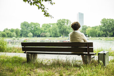 Back view of senior woman sitting on a bench - UUF004543