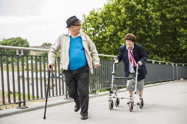 Senior couple with walking stick and wheeled walker - UUF004561