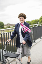 Smiling senior woman walking with wheeled walker - UUF004563