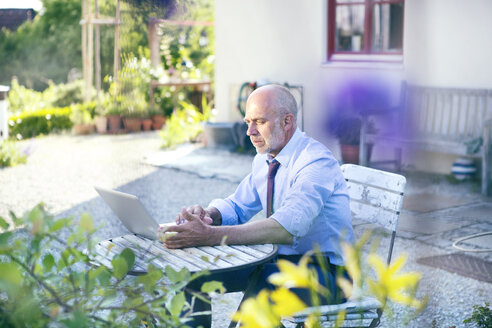 Businessman working with laptop on a terrace - MAEF010633
