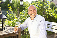 Portrait of happy man sitting with glass of white wine relaxing in the garden - MAEF010646