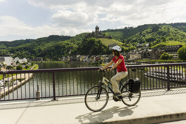 Germany, Cochem, cyclist passing bridge over Moselle - UUF004568