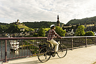 Germany, Cochem, cyclist passing bridge over Moselle - UUF004571