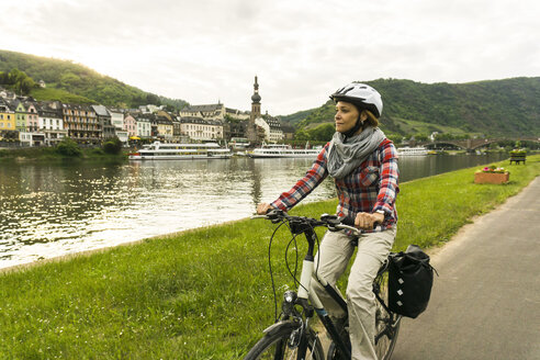 Germany, Cochem, woman riding bycicle along riverside of Moselle - UUF004583
