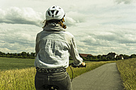 Woman riding bicycle at countryside - UUF004574